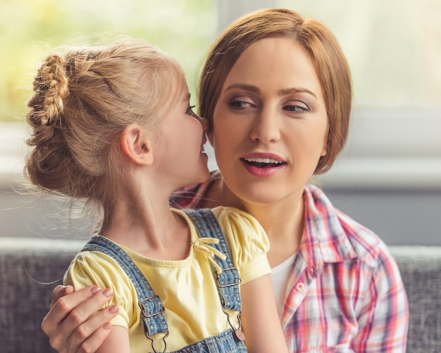 Cute little girl is whispering something in her mother. Premium Photo