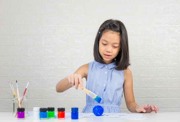 Cute little girl learning solar system making model with painting on foam ball Premium Photo