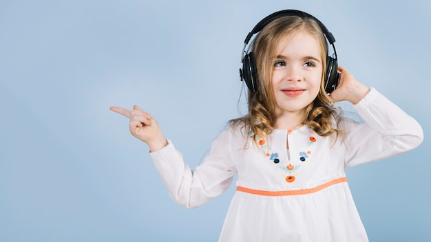 Cute little girl listening music on headphone pointing her finger at something Free Photo