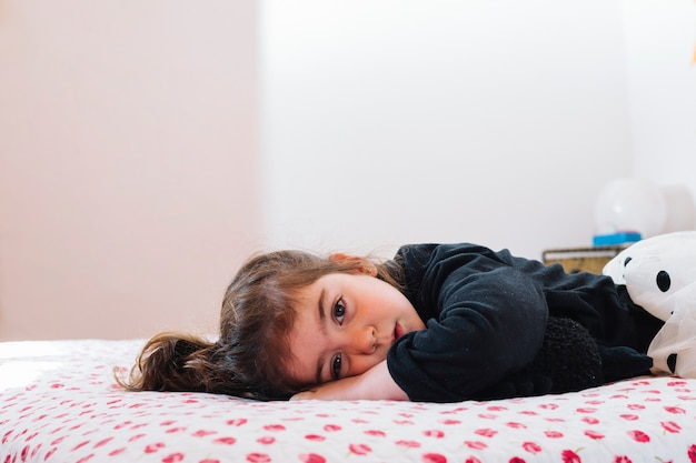 Cute little girl lying on bed Free Photo