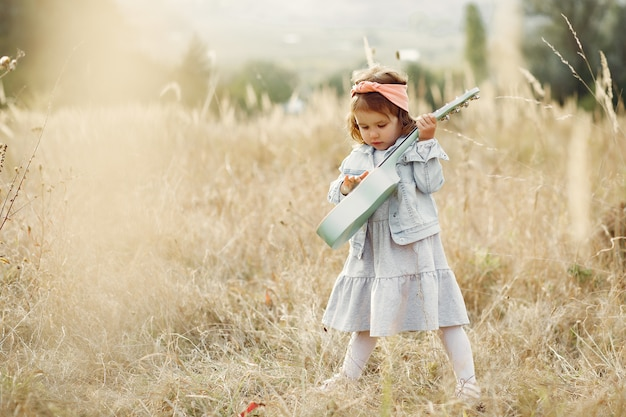 Cute little girl in a park playing on a guitar Free Photo