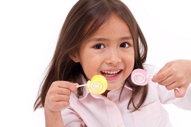 Cute little girl playing, eating sugar jelly sweet candy Premium Photo
