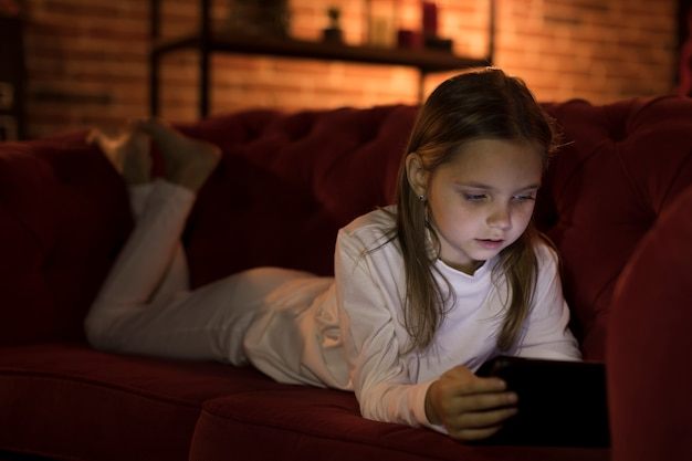 Cute little girl playing a game on her phone Free Photo