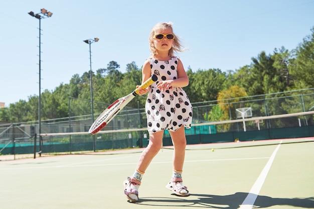 Милая маленькая девочка играет в теннис на теннисном корте снаружи. Бесплатные Фотографии
