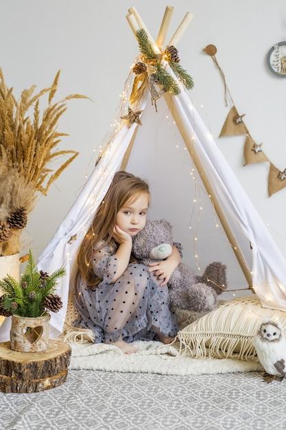집에서 Wigwam에 테 디 베어와 함께 연주 귀여운 소녀. 새해 장식. 프리미엄 사진