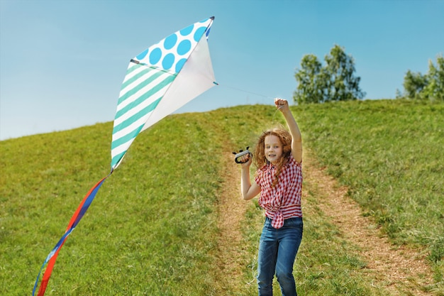 Cute little girl  playing with a flying kite. Premium Photo