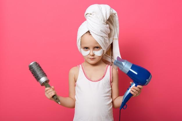 Милая маленькая девочка позирует с круглой щеткой и феном в руках Бесплатные Фотографии
