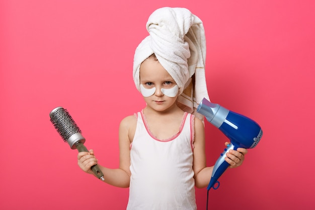 Cute little girl posing with round brush dryer and hairdryer in hands Free Photo