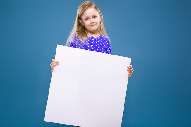 Cute little girl in purple dress holds empty blank placard Premium Photo