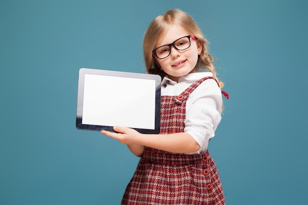 Cute little girl in red dress, white shirt and glasses holds empty tablet Premium Photo