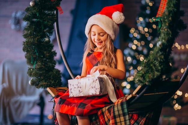 Cute little girl in santa hat unpacking christmas present Free Photo