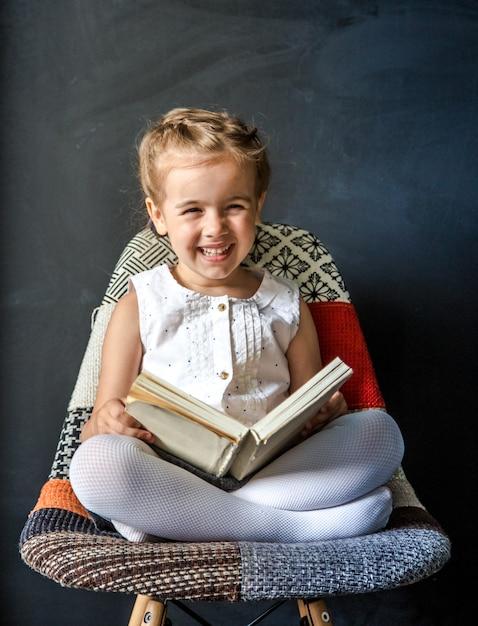 Bambina sveglia che si siede su una bella sedia con un libro in mano, il concetto di educazione e vita scolastica Foto Gratuite