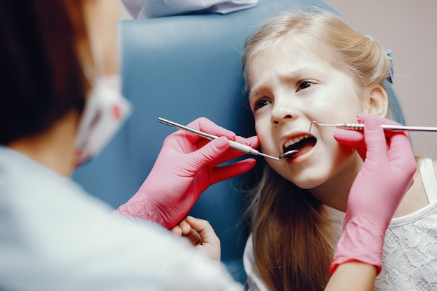 Cute little girl sitting in the dentist's office Free Photo