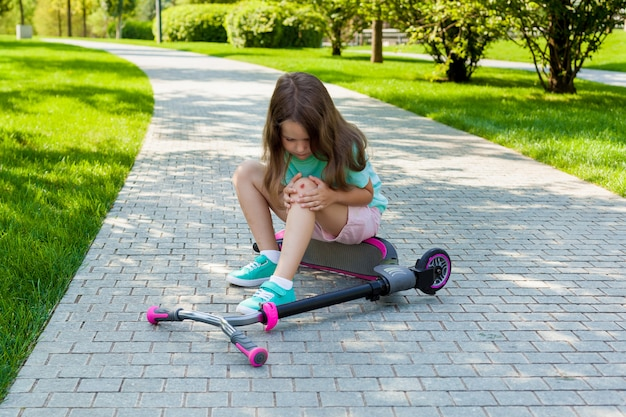 Cute little girl sitting on the ground after falling off her scooter at summer park. Premium Photo