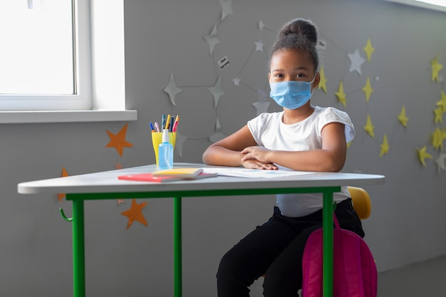 Cute little girl sitting at her desk in classroom Free Photo