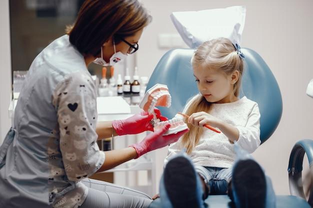 Милая маленькая девочка сидит в кабинете стоматолога Бесплатные Фотографии