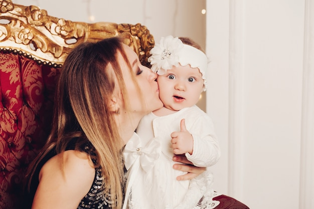 Cute little girl sitting with mother. christmas time. Premium Photo