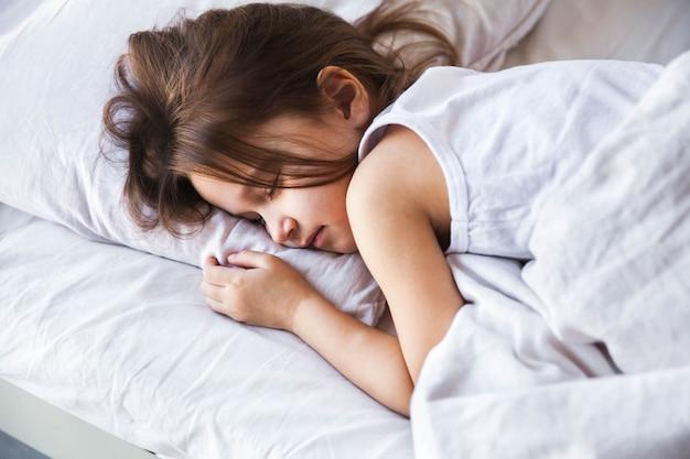 自宅のベッドで寝ているかわいい女の子 Premium写真