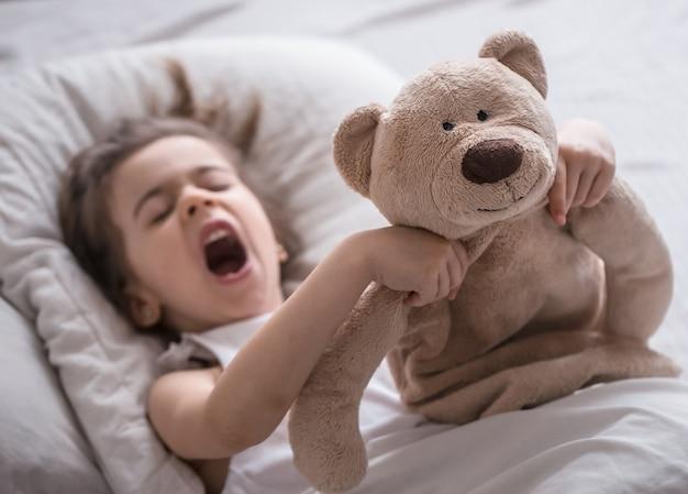 かわいい女の子が柔らかいクマのおもちゃ、子供たちの休息と睡眠の概念と白い居心地の良いベッドで甘く眠る Premium写真