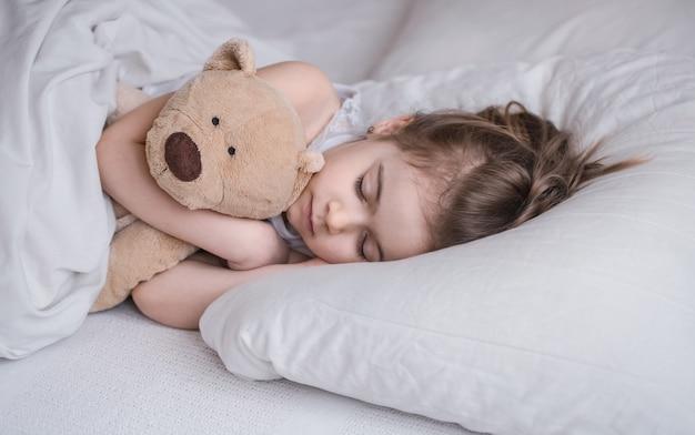 かわいい女の子が柔らかいクマのおもちゃ、子供たちの休息と睡眠の概念と白い居心地の良いベッドで甘く眠る 無料写真