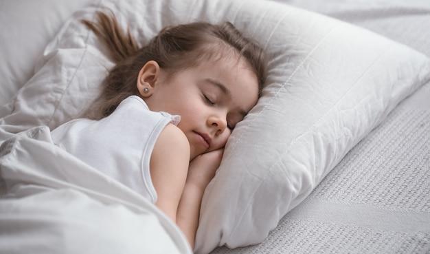 Милая маленькая девочка сладко спит в постели Бесплатные Фотографии