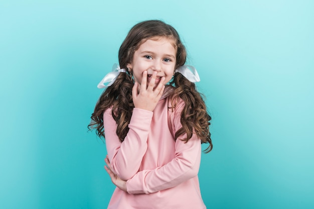 Cute little girl smiling on blue background Free Photo
