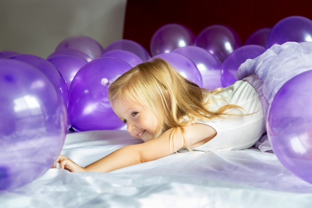 Cute little girl in stylish dress celebrating birthday day with purple balloons Premium Photo