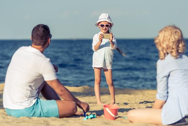 Cute little girl in sun glasses is taking photo. Premium Photo
