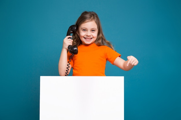 Cute little girl in tee shirt with brown hair hold clean paper and have a phone talk Premium Photo