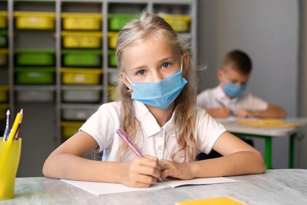 Милая маленькая девочка в медицинской маске Premium Фотографии
