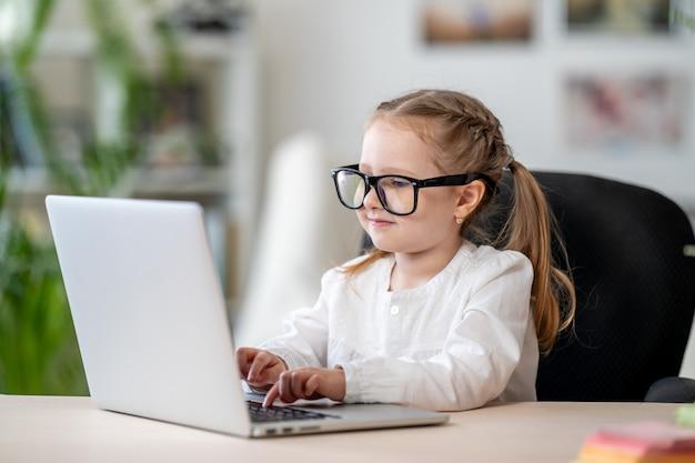 ラップトップデジタルeラーニングコンセプトを使用して眼鏡をかけているかわいい女の子 Premium写真