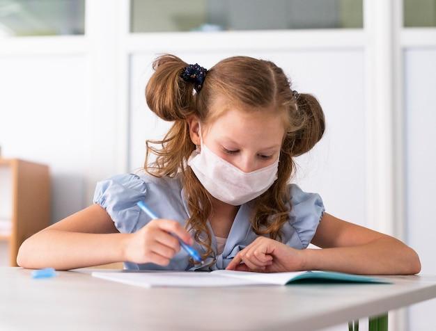 Bambina sveglia che indossa una mascherina medica durante la scrittura Foto Gratuite
