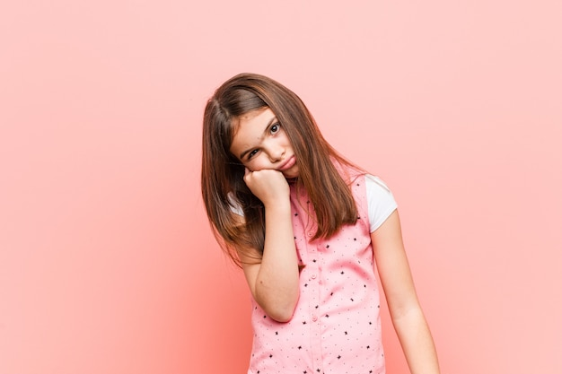 Cute little girl who feels sad and pensive, looking at copy . Premium Photo