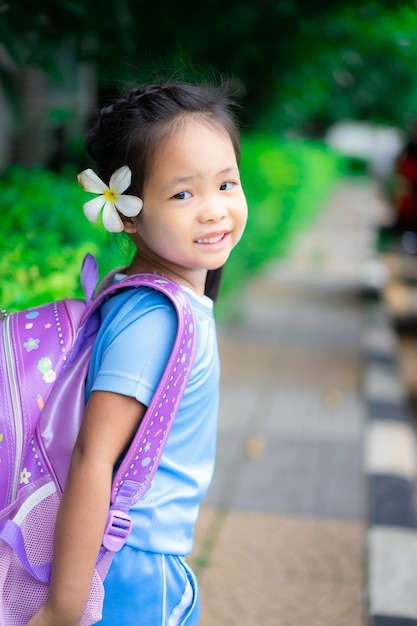 Cute little girl with backpack walking in the park ready back to school Premium Photo