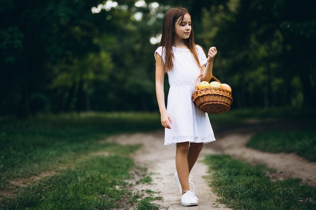 Cute little girl with basket of fruit Free Photo