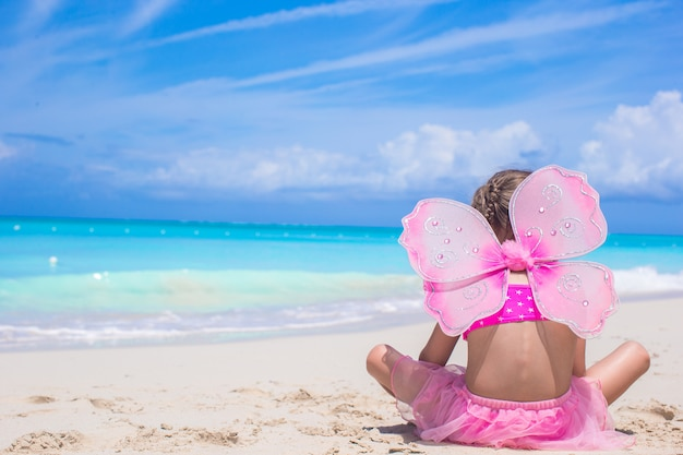 Cute little girl with butterfly wings on beach vacation Premium Photo