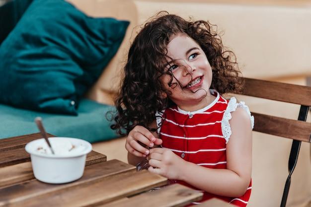 야외 레스토랑에 앉아 곱슬 머리를 가진 귀여운 어린 소녀. 카페에서 아이스크림을 먹는 예쁜 아이의 초상화. 무료 사진