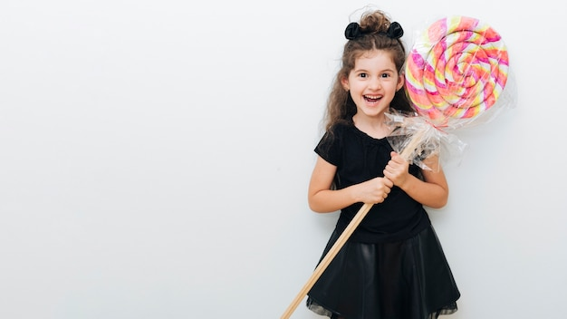 Cute little girl with giant lollipop and copy space Free Photo