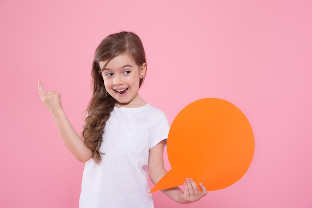 Cute little girl with an icon of a speech on a pink wall Free Photo