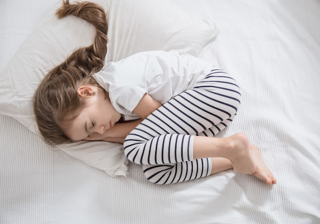 Cute little girl with long hair sleeping in bed Free Photo