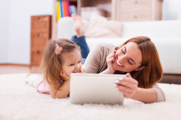 Cute little girl with mom using digital tablet at home Free Photo