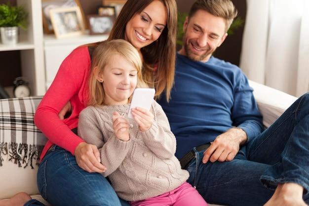 Bambina sveglia con i genitori che giocano dal telefono cellulare a casa Foto Gratuite