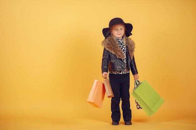 노란색 배경에 쇼핑백과 귀여운 소녀 무료 사진