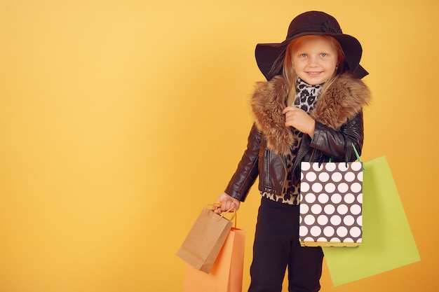 Cute little girl with shopping bags on a yellow background Free Photo