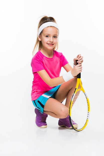 Cute little girl with tennis racket in her hands on white Premium Photo