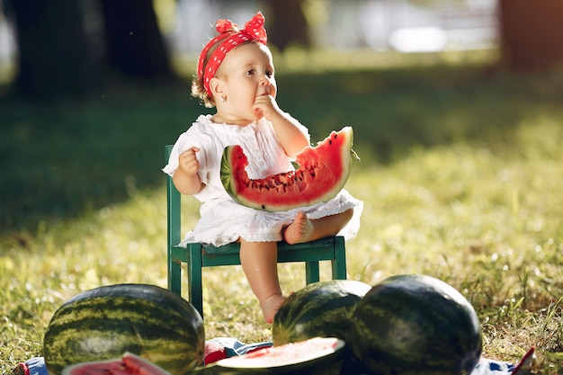 Cute little girl with watermelons in a park Free Photo