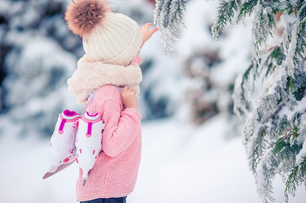 Cute little kid girl is going skate outdoors. Premium Photo