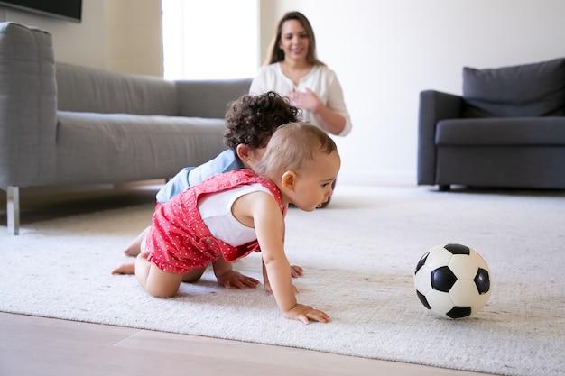 카펫에 크롤 링 하 고 축구 공을 가지고 노는 귀여운 작은 아이. 바닥에 앉아 웃 고 아이들을보고 돌보는 어머니. 선택적 초점. 실내 가족, 주말 및 어린 시절 개념 무료 사진