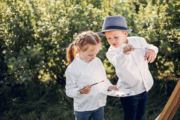 Cute little kids painting in a park Free Photo