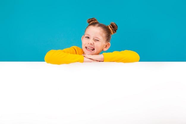 Милая маленькая рыжеволосая девушка в желтом пуловере Premium Фотографии